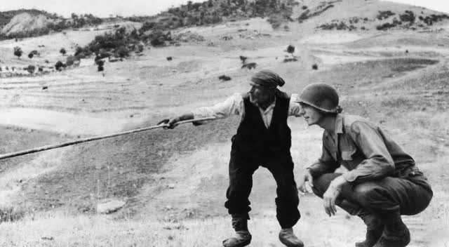 Un contadino siciliano indica a un militare americano le posizioni dell'Asse
