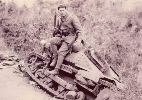 Un soldato greco seduto sullo scafo di un carro L3 abbandonato durante la ritirata degli italiani dall'Epiro.jpg
